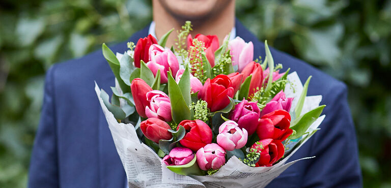 Man holding a red and pink bouquet of tulips