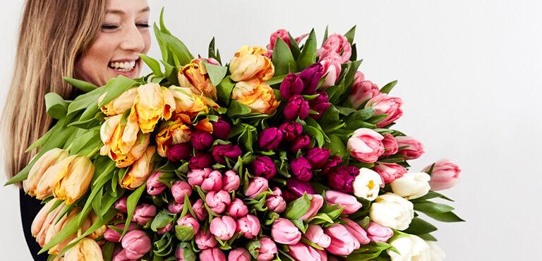 Vrouw met een groot kleurrijk tulpenboeket in haar armen